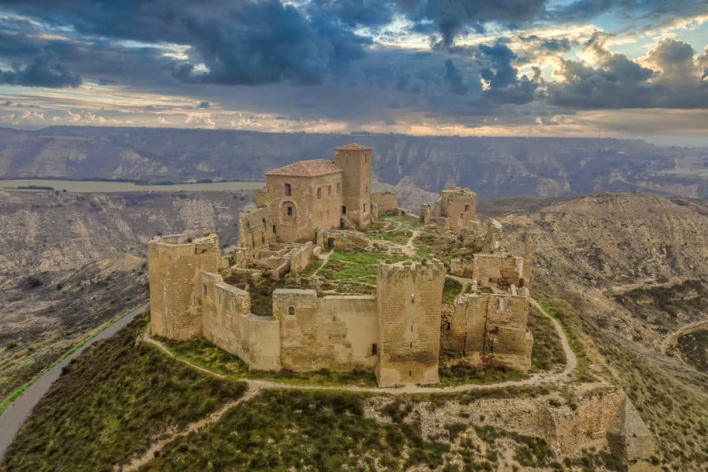 Aerial view of the partially restored medieval Gothic castle ruin of Montearagon near Huesca Spain with dramatic sunset sky