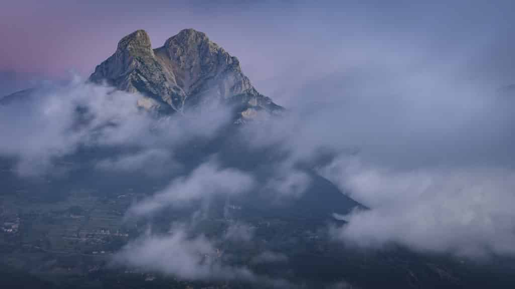 Pedraforca in a summer sunrise with low clouds over the Saldes Valley, seen from near La Palomera (Berguedà, Catalonia, Spain, Pyrenees)