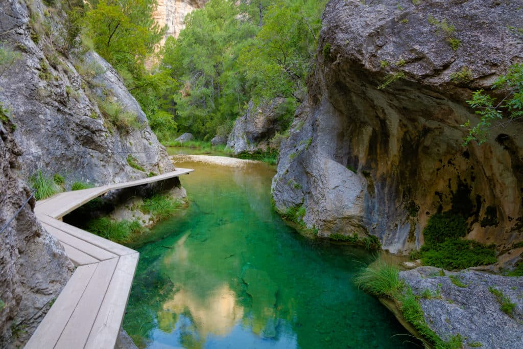 The Matarranya river runs between large rocks where the trees hang, forming a spectacular landscape with its transparent green waters. The Parrizal. Beseit, Matarranya, Aragon, Spain